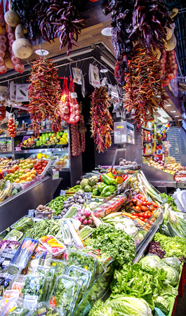 bundles: SPAIN, BARCELONA, JUNE, 29, 2015 - La Boqueria market with vegetables and bundles of hot peppers in Barcelona, Spain. La Boqueria market, Europes largest and most famous food markets.