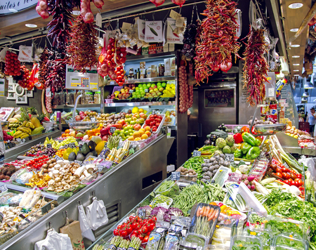 boqueria: SPAIN, BARCELONA, JUNE, 29, 2015 - La Boqueria market with vegetables and bundles of hot peppers in Barcelona, Spain. La Boqueria market, Europes largest and most famous food markets.