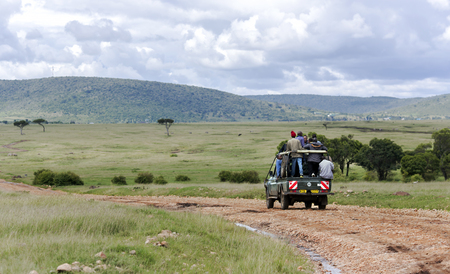 quantities: AFRICA, KENYA, MAY, 05, 2016 - Through the Masai Mara National Park Jeep carries local African residents, who crowd into the car in extreme quantities. Kenya, Africa