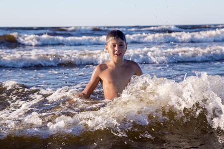 kiddies: Pretty teenager playing in foamy waves of the Baltic Sea in Jurmala, Latvia