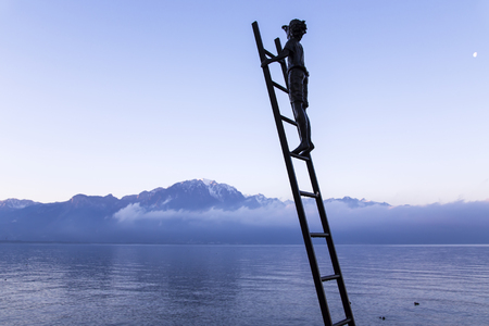 december sunrise: SWITZERLAND, MONTREUX, DECEMBER, 28, 2015 - Bronze statue of boy on the stair of meet a sunrise on a background Swiss Alps and ashore of lake Geneva at Montreux.