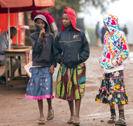 poorly: AFRICA, TANZANIA, MAY, 09, 2016 - Three african poorly dressed young girls on the streets in Arusha. Arusha is located below Mount Meru in the eastern branch of the Great Rift Valley and the capital of the Arusha Region. Editorial