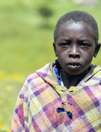 poorly: AFRICA, TANZANIA, MAY, 10, 2016 - African poorly dressed teenager attentively looks far walking away in the Ngorongoro Crater. Tanzania.