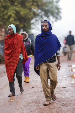 capes: AFRICA, TANZANIA, ARUSHA, MAY, 10, 2016 - Typical street scene in Arusha. African men walking on the street in colorful capes of Maasai Mara. Arusha is located below Mount Meru in the eastern branch of the Great Rift Valley Editorial