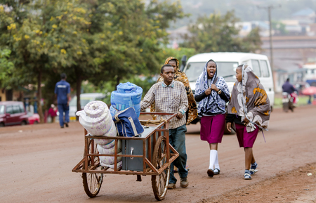 capes: AFRICA, TANZANIA, MAY, 09, 2016 - Typical street scene in Arusha. Mostly a wheelbarrow is the only means of transportation of luggage. Arusha is located below Mount Meru in the eastern branch of the Great Rift Valley