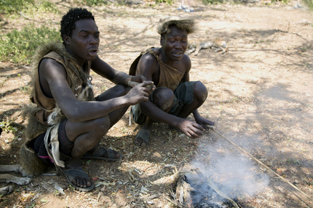 AFRICA, TANZANIA, MAY, 10, 2016 - Two Hazabe bushman of the hadza tribe squatting near the fire and trying to light his pipe. Hadzabe tribe threatened by extinction in Tanzania, Africa Editorial