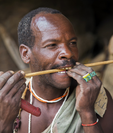 AFRICA, TANZANIA, MAY, 10, 2016 - Hazabe bushman of the hadza tribe in traditional beaded jewelry, checks arrows for durability of for hunting. Hadzabe tribe threatened by extinction in Tanzania, Africa