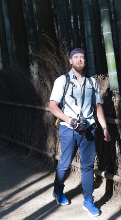 sways: JAPAN, KYOTO, APRIL, 03, 2017 - A young man with beard and a camera is surprised by a beautiful japan bamboo forest in Arashiyama, near Kyoto, Japan.The green grove is relaxing and the the bamboo sways and whistles with the wind.