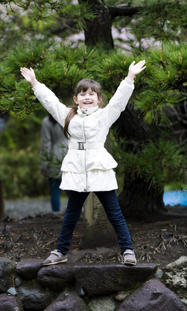 A sweet happy little girl laughs, raising his hands against the background of Japanese pine in Kyoto, Japan Foto de archivo