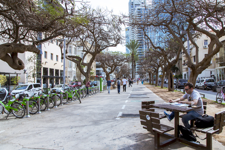 ISRAEL, TEL-AVIV, FEBRUARY, 23, 2016 - Quiet street in the center of new Tel Aviv. A man reads a newspaper at a table on a warm February morning in Tel Aviv, Israel.