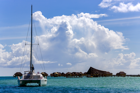 Lonely catamaran on the background of the island of the Polynesia. Stock Photo