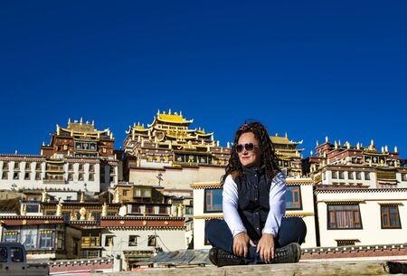 Woman travel photographer on background Songzanlin Monastery 스톡 콘텐츠