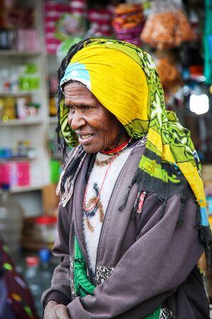 INDONESIA, PAPUA NEW GUINEA, WAMENA, IRIAN JAYA, AUGUST 20, 2019: Papuan woman in a bright yellow turban on the market in Wamena, Papua New Guinea, Indonesia