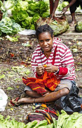 INDONESIA, PAPUA NEW GUINEA, WAMENA, IRIAN JAYA, AUGUST 20, 2019: Papuan woman crochets a multi-colored bag in the market in Wamena, Papua New Guinea, Indonesia