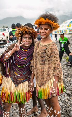 INDONESIA, PAPUA NEW GUINEA, WAMENA, IRIAN JAYA, AUGUST 20, 2018: Two woman of a papuan tribe in a beautiful crown from bird feathers on Baliem Valley festival in Wamena, Papua New Guinea.