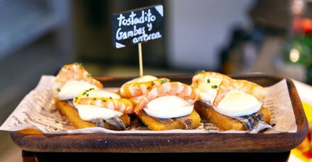 Appetizing spanish tapas with anchovies and shrimp close-up in the restaurant of San Sebastian, Donostia, Spain