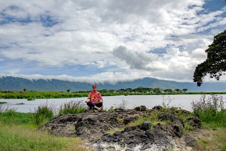 Woman traveler resting on the shore of a beautiful lake in the Ngorongoro valley, Tanzania, Africa