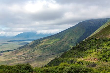 Ngorongoro valley with mountains in the background on a cloudy day, Tanzania, Africa Banco de Imagens
