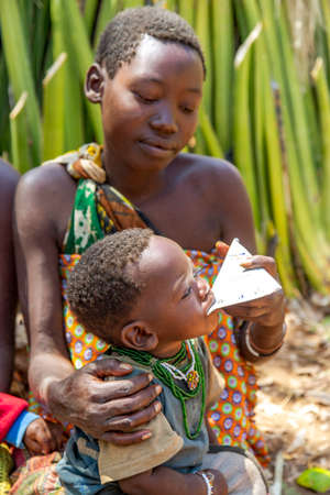 AFRICA, TANZANIA, MAY, 10, 2016 - Woman with small children of the Hadzabe tribe feeds her baby milk from the package. Hadzabe tribe threatened by extinction in Tanzania, Africa Editorial