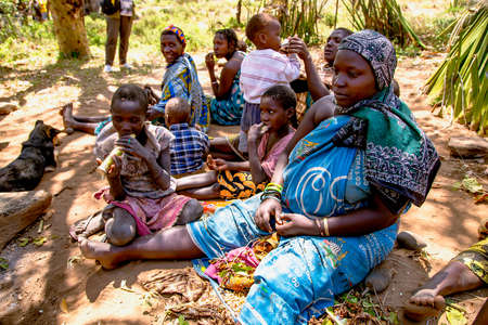 AFRICA, TANZANIA, MAY, 10, 2016 - Woman with children of the Hadzabe tribe sitting on the ground. Hadzabe tribe threatened by extinction in Tanzania, Africa Editorial