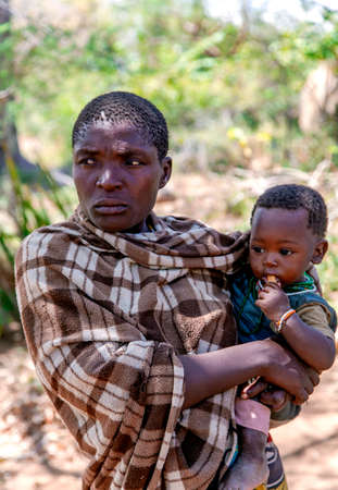 AFRICA, TANZANIA, MAY, 10, 2016 - Woman with small children of the Hadzabe tribe. Hadzabe tribe threatened by extinction in Tanzania, Africa