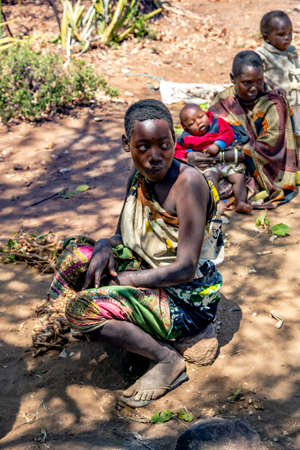 AFRICA, TANZANIA, MAY, 10, 2016 - Womans with small children of the Hadzabe tribe sitting on the ground. Hadzabe tribe threatened by extinction in Tanzania, Africa