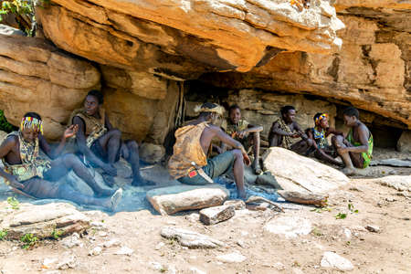 AFRICA, TANZANIA, MAY, 10, 2016 - Hadzabe tribe mens shelter from the hot sun in the shadow of a rock. Hadzabe tribe threatened by extinction in Tanzania, Africa