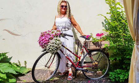 Nice girl with curly hair near a bicycle decorated with flowers Banco de Imagens