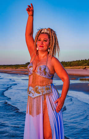 Portrait of a pretty woman with curly hair in oriental dance costume on the shores of the Baltic Sea at sunset in Riga, Latvia
