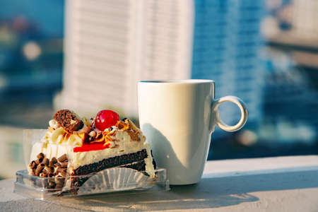 White large cup of coffee and a beautiful cake with chocolate and cherry - morning breakfast on the balcony