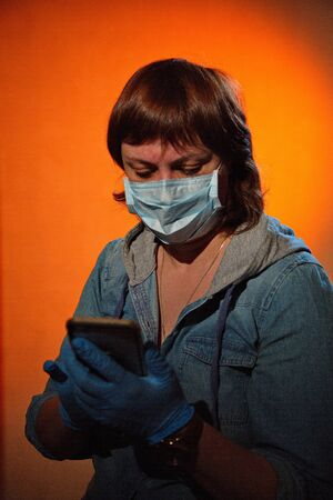 Portrait of a young woman in a medical mask with a phone.