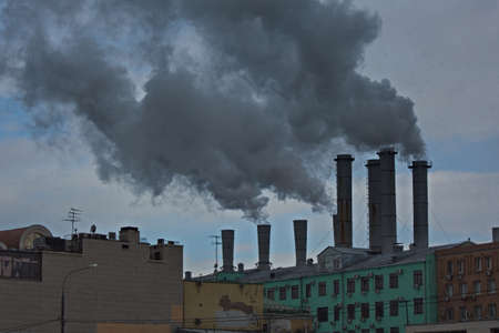 Smoking chimneys of a Moscow thermal power station in the city center. Banco de Imagens