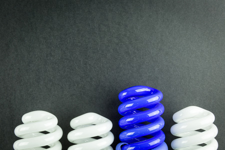 differentiate: Energy saving light bulbs business concept of Differentiation on black paper