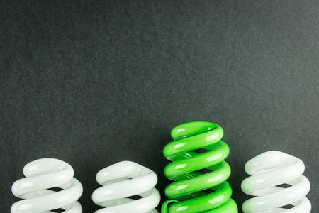 검은 종이에 에너지 절약 전구 차별화의 비즈니스 개념