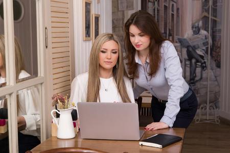 Deux femmes d'affaires sérieuses réussies au processus de travail en regardant l'écran de leur ordinateur portable et en discutant d'un problème