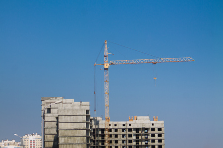 tower crane on a construction site on the blue sky background
