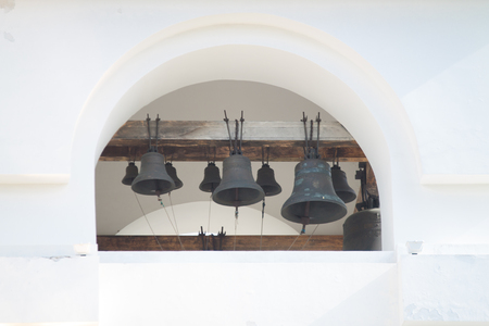 church bells of different sizes on a white wall background