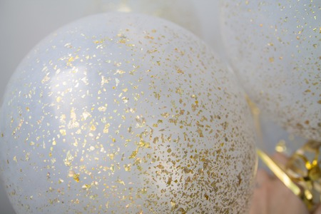 a bunch of transparent balloons with golden dust within on a white blurry background 版權商用圖片