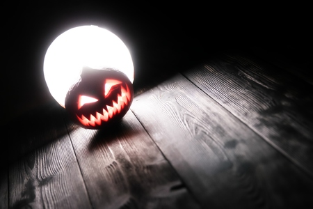 Halloween pumpkin Jack-o-lantern on the dark wooden background with a scary face as a symbol of halloween night with the concept full moon behind it. 스톡 콘텐츠