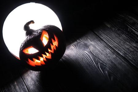 Halloween pumpkin Jack-o-lantern on the dark wooden background with a scary face as a symbol of halloween night with the concept full moon behind it. 免版税图像