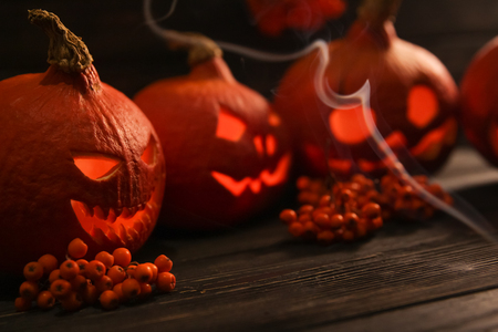 scary halloween pumpkin lanterns with luminous scary faces with rowanberries on a wooden background and the clouds of smoke in front of them