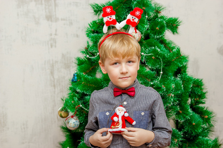 portrait of a boy with funny glasses and christmas toys decorating cristmas tree and have fun