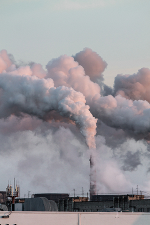 Vertical image of industrial chimneys with heavy smoke causing air pollution problem Standard-Bild - 114019835