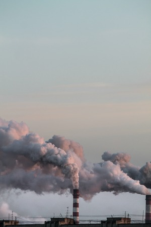 Vertical image of industrial chimneys with heavy smoke causing air pollution problem