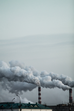 Vertical image of industrial chimneys with heavy smoke causing air pollution problem Standard-Bild - 114019842
