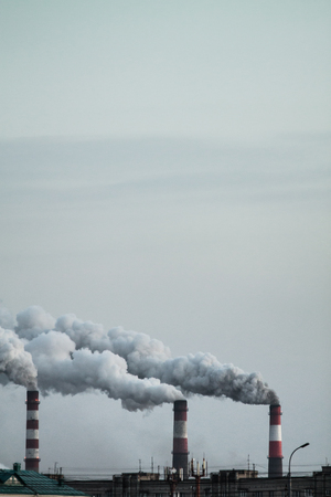 Vertical image of industrial chimneys with heavy smoke causing air pollution problem Standard-Bild - 114019846