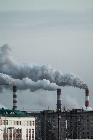 Vertical image of industrial chimneys with heavy smoke causing air pollution problem Standard-Bild - 114019970