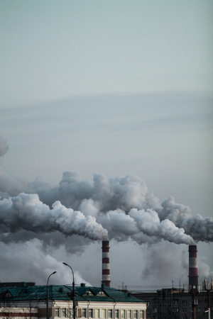 Vertical image of industrial chimneys with heavy smoke causing air pollution problem Standard-Bild - 114019971