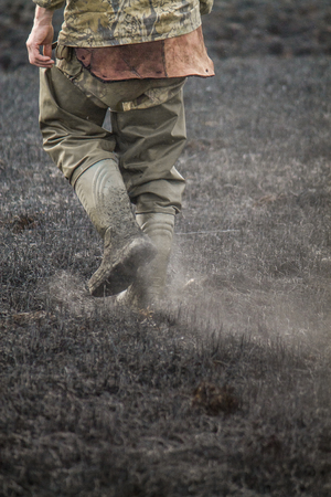 Legs in boots walking on burnt withered grass with ashes in the air, environmental problem of fires