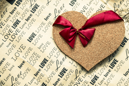 cork heart with a red ribbon on it laying on craft paper with lots of inscriptions of love words on it as a background